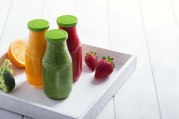 果物と野菜の瓶の中の新鮮なイチゴ、オレンジ、ブロッコリーのスムージー