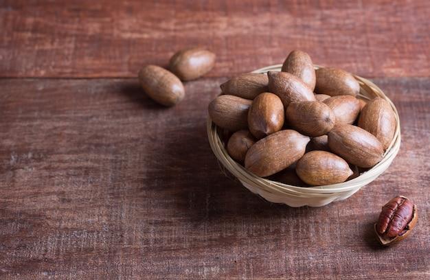 Орехи пекан в миске на деревянном столе