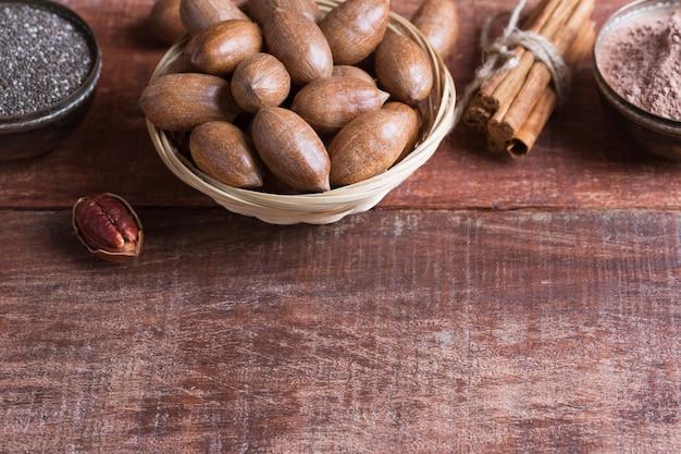Орехи пекан, семена чиа и какао в мисках на деревянном столе
