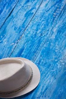 青い木製のテーブルの上の夏の帽子