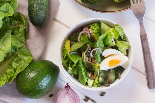 Салат из свежих зеленых листьев, лука и вареного куриного яйца