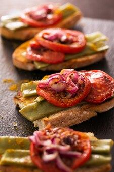 Летний бутерброд с жареным красным луком, помидорами и фасолью. выборочный фокус