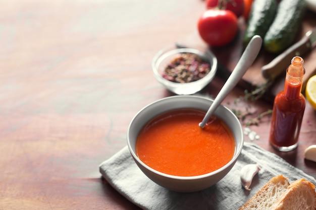 木製の表面に新鮮な野菜とガスパチョスープ