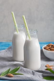 Миндальное молоко в двух бутылках на синем деревянном деревенском столе