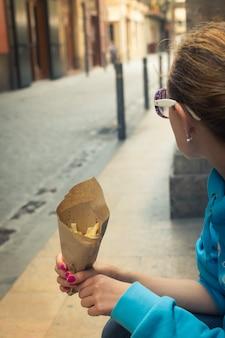 Женщина, держащая картофель фри в руке на улице