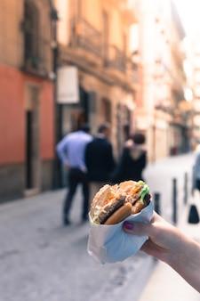 Женщина держит в руках гамбургер