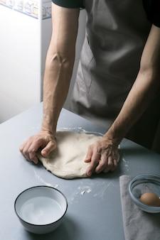 家庭の台所で男は小麦粉で生地を準備し、有機パン、パン、パスタを作る