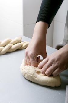 家庭の台所で女性が小麦粉で生地を準備し、有機パン、パン、パスタを作る