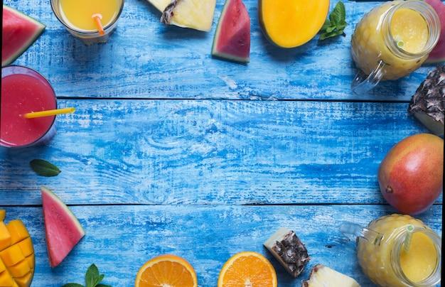 Свежий ананас, манго и арбузный коктейль в двух стаканах с фруктами на синем деревянном деревенском фоне
