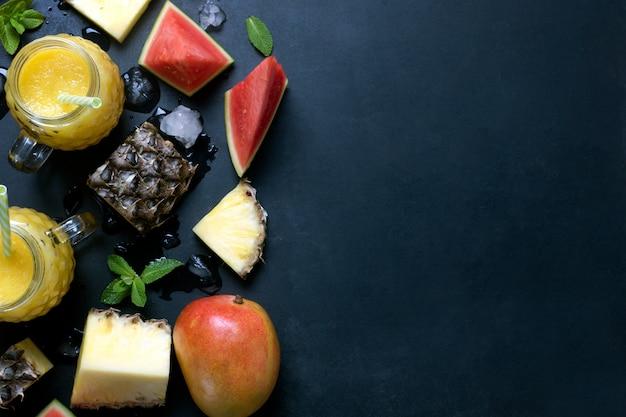 Свежий коктейль из ананаса и манго в очках с фруктами на черном деревенском фоне