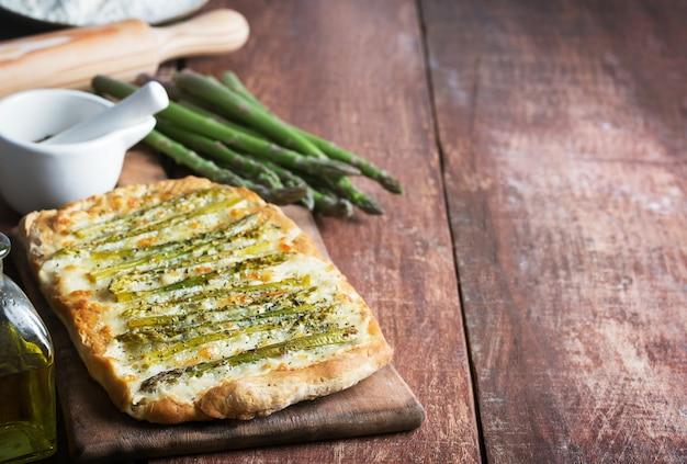 Спаржа зеленая пицца с зеленью и моцареллой. копировать пространство