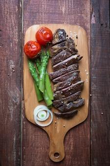 軽いまな板木製の素朴なテーブルの上の牛肉のグリルステーキ