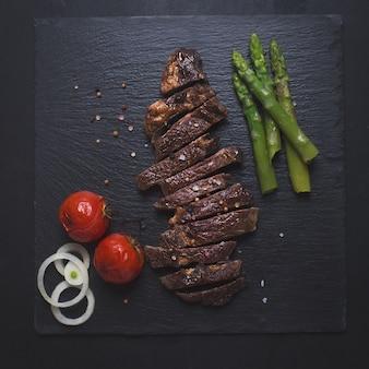 黒いテーブルの上の牛肉のグリルステーキ