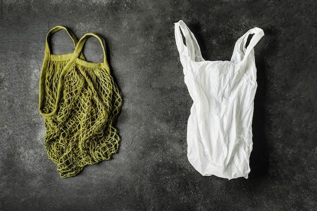 緑のひも袋と白いビニール袋。プラスチックの概念。環境製品を選択してください。