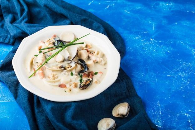 白いプレートのクラムチャウダー。主な成分は、貝、スープ、バター、ジャガイモ、玉ねぎです。