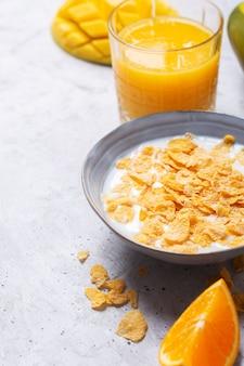 さまざまな黄色の成分-シリアルと果物で構成される朝食。灰色の背景