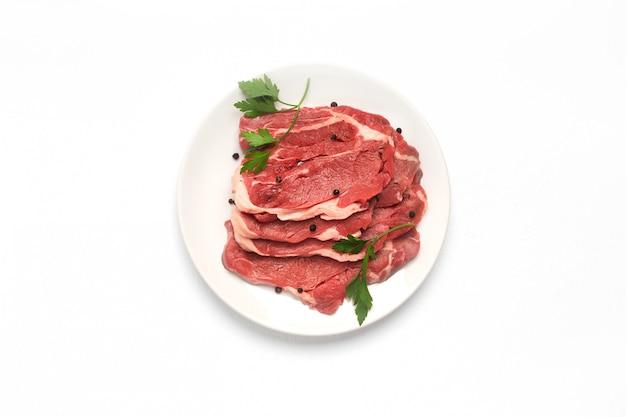 白い背景に、平面図上で分離新鮮な生の牛肉ステーキ