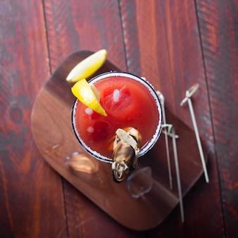 氷、塩、木製のテーブルにガラスのスナックとカクテルブラッディメアリー。フラットレイ