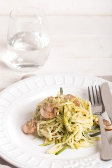 Тарелка спагетти, приготовленная из цуккини и грибным соусом на деревянном столе
