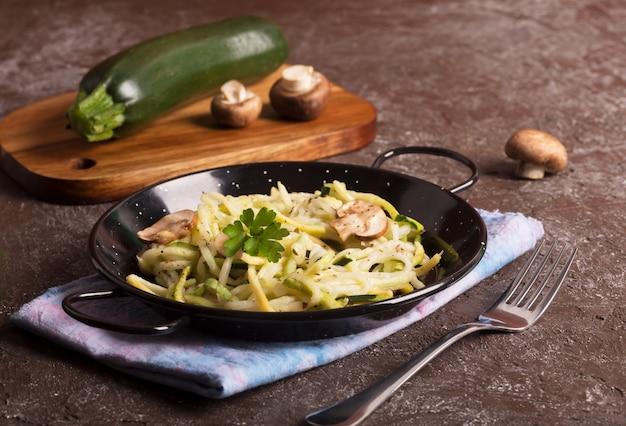 Кастрюля спагетти, приготовленная из цуккини и грибного соуса на деревянном столе