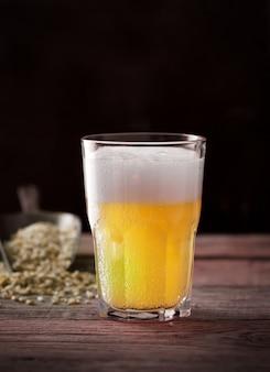 ガラス、暗い木製のテーブルで自家製クラフトビール