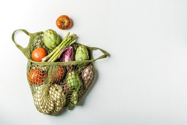 白いテーブルの上の緑のひもバッグで新鮮な野菜。カリフラワー、トマト、アーティチョーク、アスパラガス、ズッキーニ。
