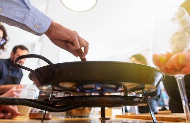 Женщина и мужчина учат своих друзей готовить еду - пиццу или пирог. люди готовят на кухне вместе. кулинарный мастер-класс