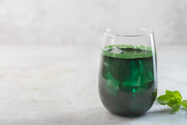 Зеленый напиток, приготовленный из одноклеточных зеленых водорослей хлореллы. детокс суперпродукт в стакане с копией пространства