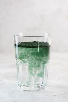 Зеленый напиток, приготовленный из одноклеточных зеленых водорослей хлореллы. детокс суперпродукт в стакане