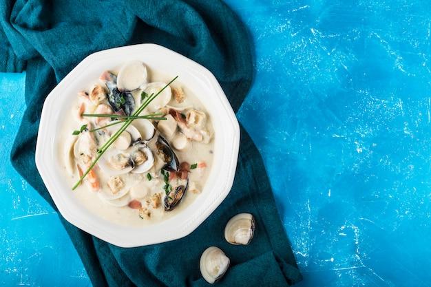 白い皿にクラムチャウダー。主な材料は貝、スープ、バター、ジャガイモ、タマネギです。