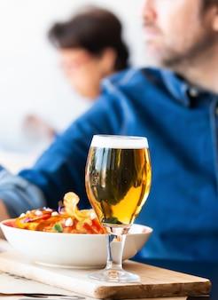 ビールと木製のテーブル上のチップのガラス