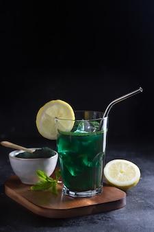 Зеленый напиток, приготовленный из одноклеточных зеленых водорослей хлореллы. детокс суперпродукт в стакане. темный и угрюмый