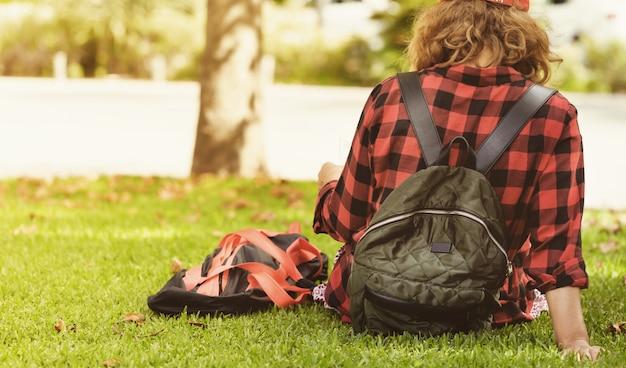 草の上に座って地図を読むバックパックを持つ若い女性
