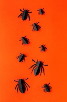 オレンジ色の背景に紙のクモ