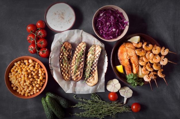 Подготовленные баклажаны, морепродукты и ингредиенты для приготовления пищи на черной поверхности