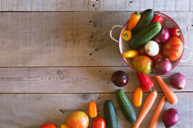 木製の背景に新鮮な有機野菜。上面図