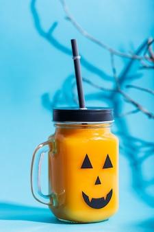 ハロウィーンの健康的なカボチャまたはニンジンとトマトは、青色の背景に怖い顔でガラスの瓶に飲む