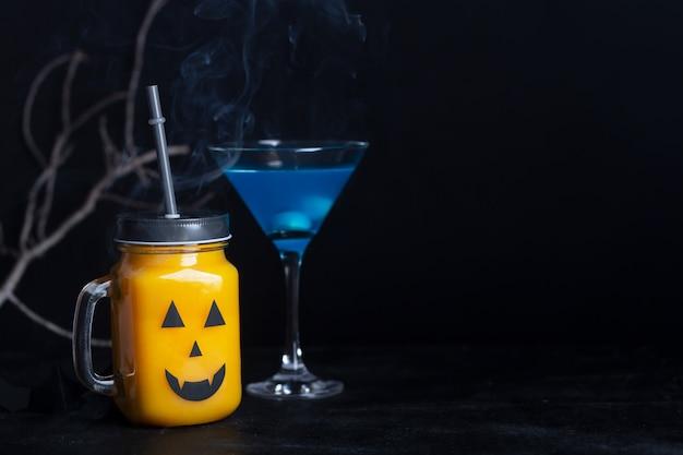 黒い背景に怖い顔でガラスの瓶にハロウィーンの健康的なカボチャやニンジンを飲む