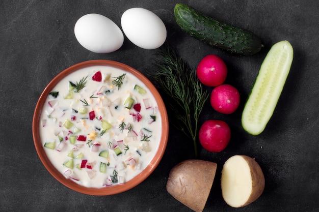 オクローシカ。テーブルの上の野菜と伝統的なロシアの夏のヨーグルトの冷たいスープ