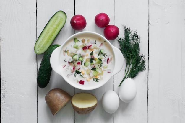 オクローシカ。白い木製のテーブルの上の野菜と伝統的なロシアの夏のヨーグルトの冷たいスープ