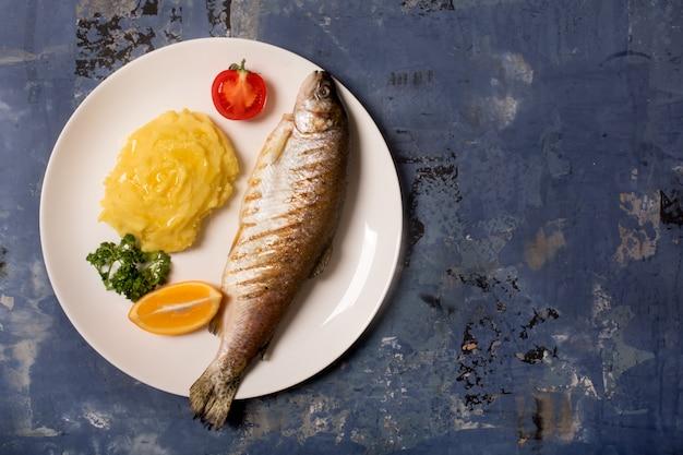 Жареная целая форель, картофель, лимон и чеснок, крупным планом. синий фон с копией пространства