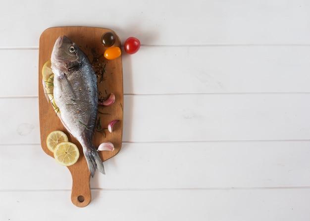 地中海の魚-ドラドとまな板の上の野菜。上面図。