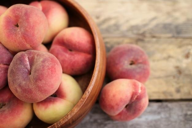 Нектарины. персики в деревянной миске на деревенский деревянный столик в деревенском стиле. сезон персиков. летние фрукты.