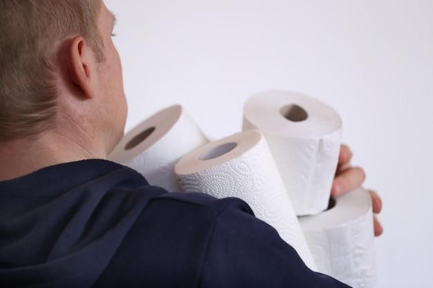 トイレットペーパーを買う。赤字。必須の製品。トイレットペーパーのロールは、白い背景の上の男性の手に設定します。コロナウイルスのコンセプト。衛生と健康