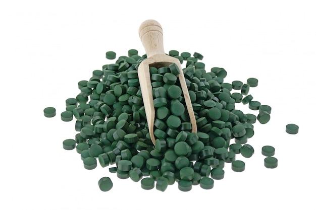 分離されたスクープで藻類のスピルリナ錠。スーパーフードのコンセプト。健康的なライフスタイルのための栄養補助食品