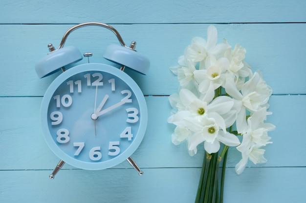 春シーズン。青い目覚まし時計、青い背景に白い水仙の花束。