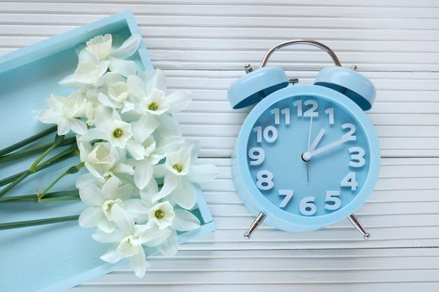 春の時間。フラットレイアウト。青い目覚まし時計、明るい背景に青いトレイに白い水仙の花束。春の気分。トップビュー
