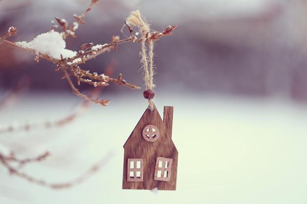 クリスマスの時期。冬と雪の枝に木製の小さな家