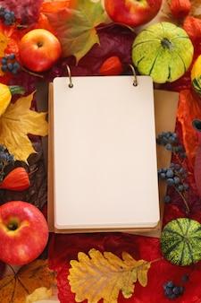 カエデの葉、リンゴ、カボチャと空のノートブック