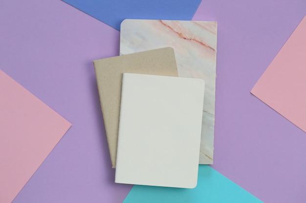 トレンドライラックピンクグラフィック背景上のノートブック。トレンディなパステル調の空の日記。パステルカラーでフラットレイアウト。トップビュー、コピースペース